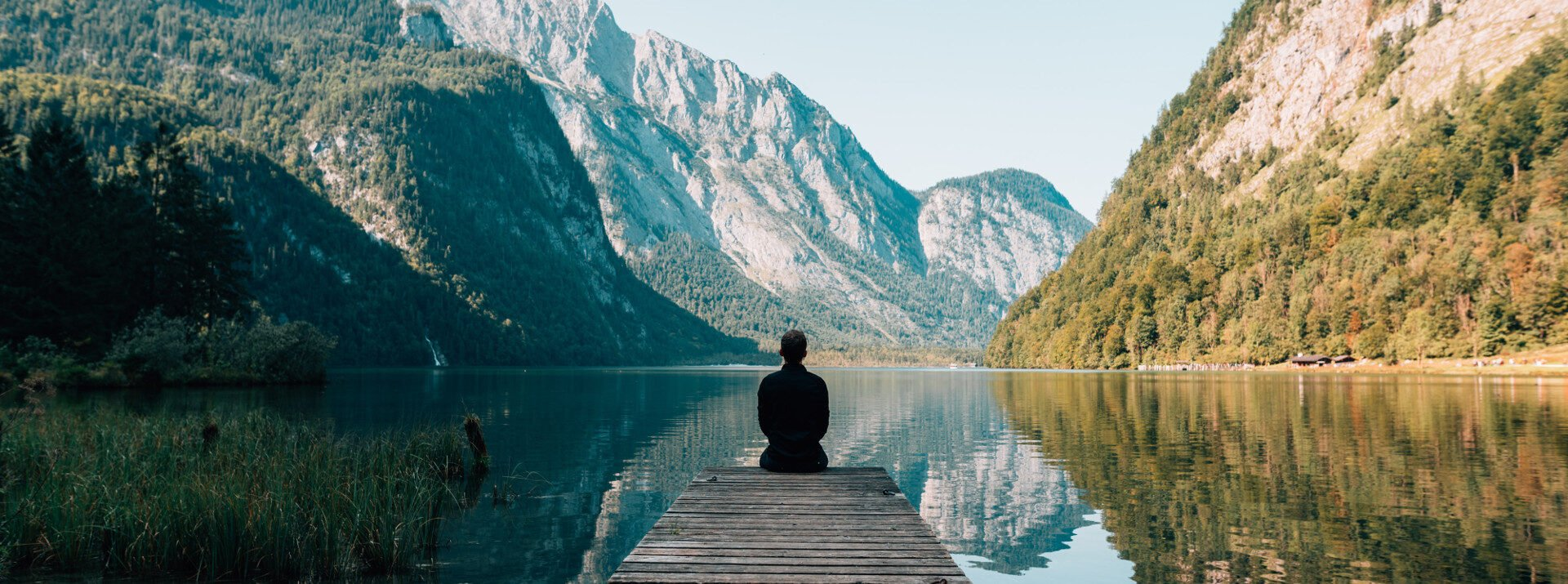 Woman sitting on a dock at a lake surrounded by mountains